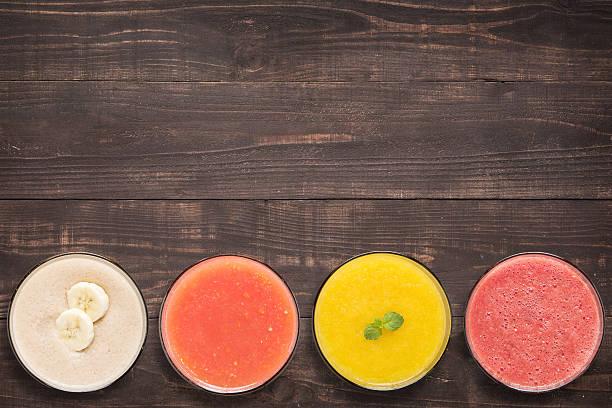 satz von frucht-smoothie oder saft in gläsern auf hölzernen - pfirsich milchshake stock-fotos und bilder
