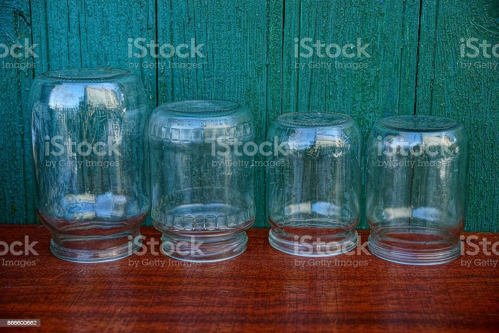 Glass jars on a red table near a green wooden wall