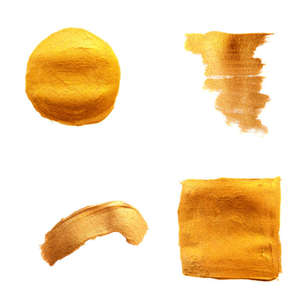 Set of golden painted brushes. Shining texture gold acrylic stain isolated on white background. stock photo