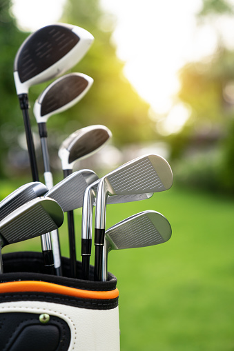 set of golf clubs over green field background,olf clubs drivers over green field background
