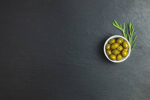 Set of green olives on plate and rosemary on a black stone background stock photo