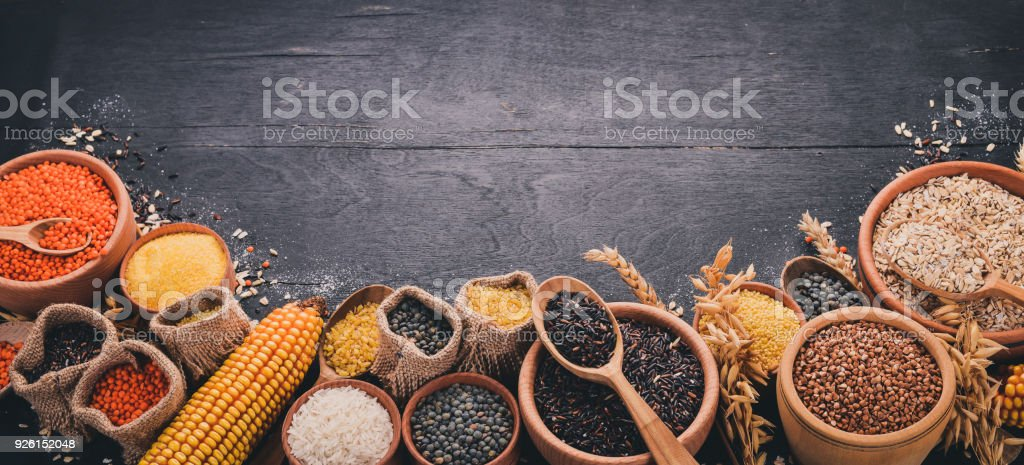 Set of Groats and Grains. Buckwheat, lentils, rice, millet, barley, corn, black rice. On a black background. Top view. Copy space. stock photo