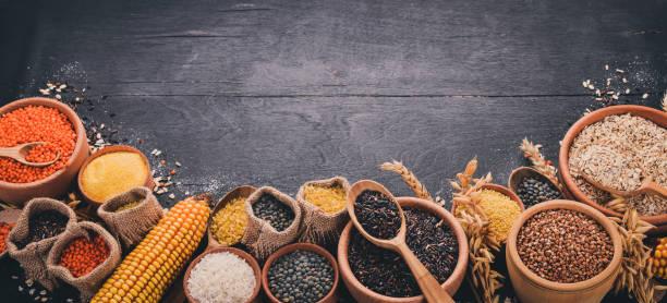 Conjunto de granos y cereales. Trigo, lentejas, arroz, mijo, cebada, maíz, arroz negro. Sobre un fondo negro. Vista superior. Copia espacio. - foto de stock