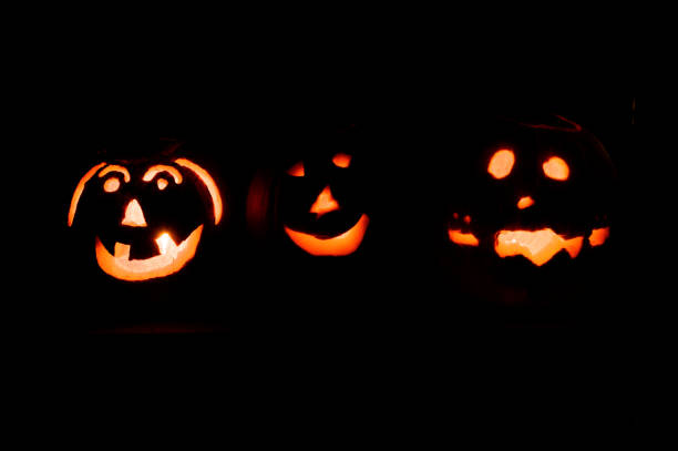 Set of Halloween jack o lantern pumpkins at night stock photo