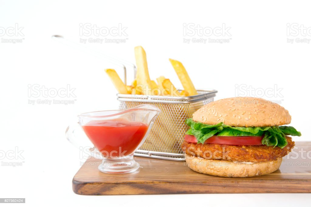 Set of hamburger and french fries with sause on wooden cutting board on white background stock photo