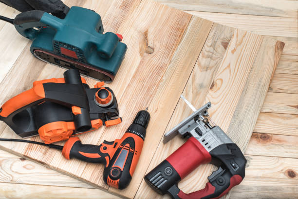 Set of handheld woodworking power tools for woodworking on light wooden background. Close up Set of handheld woodworking power tools for woodworking on light wooden background. Close up. drill stock pictures, royalty-free photos & images