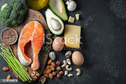 A set of healthy food for keto diet on a dark background. Fresh raw salmon steak with flax seeds, broccoli, avocado, chicken eggs, nuts and asparagus on a wooden Board. Top view with copy space.