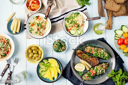 istock Set of healthy vegetarian food, salad with bulgur porridge and vegetables, stuffed eggplant, vegetables, mango, avocado and snacks on wooden table 827822624