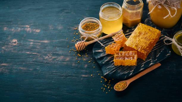 Um conjunto de produtos de mel e abelhas. Mel em favo de mel. Sobre um fundo preto de madeira. Espaço livre para texto. Vista superior. - foto de acervo