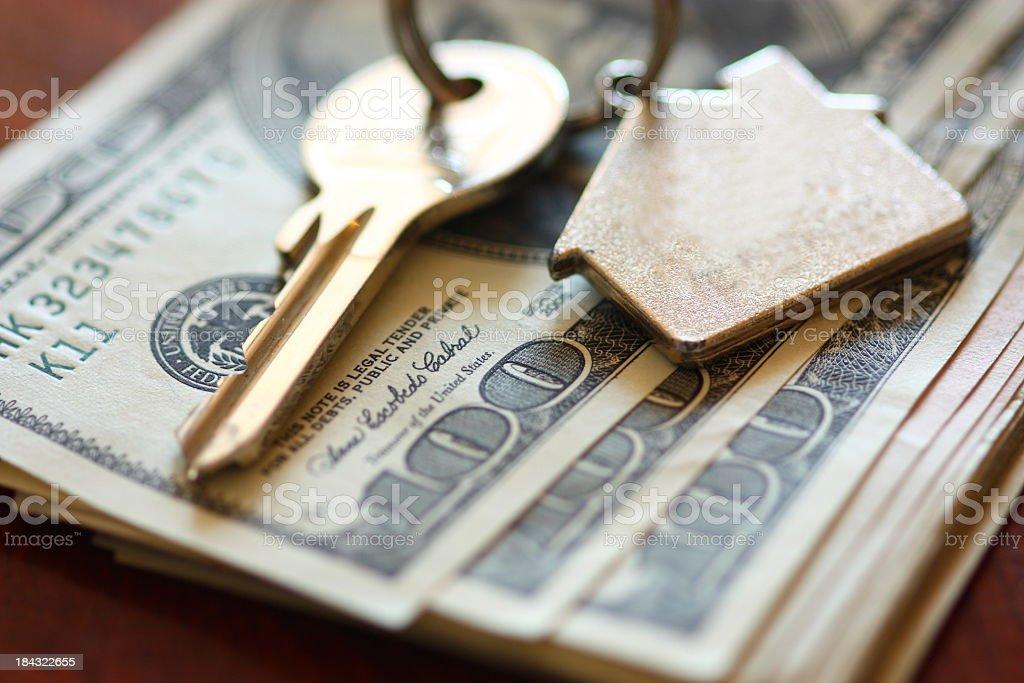 Set of house keys laying on hundred dollar bills stock photo