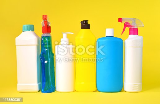 Set of household chemicals bottles on a yellow background