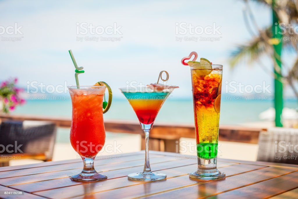 Set of iced cocktails: layered with lime, orange, blue and red cocktail on beach stock photo