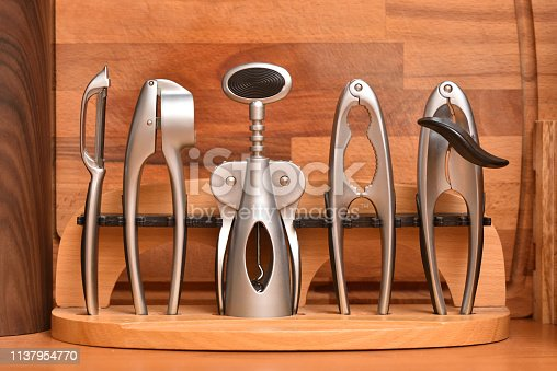A set of kitchen utensils on a wooden background, garlic press, wine opener, nutcracker, can opener, a knife for cleaning potatoes