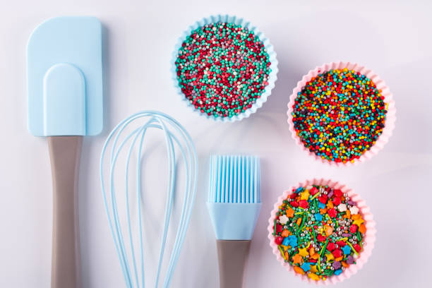 Set of kitchenware for cooking pastries and  Rainbow sprinkles for decoration on white background stock photo