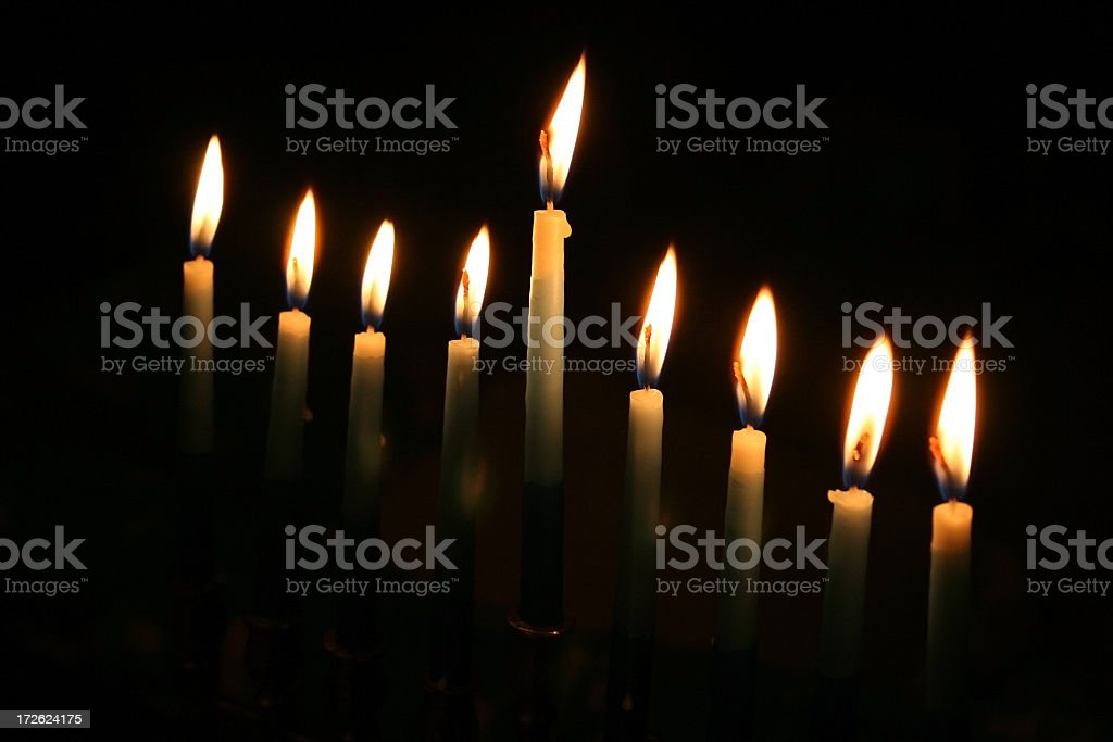 Set of lit menorah candles in the dark royalty-free stock photo