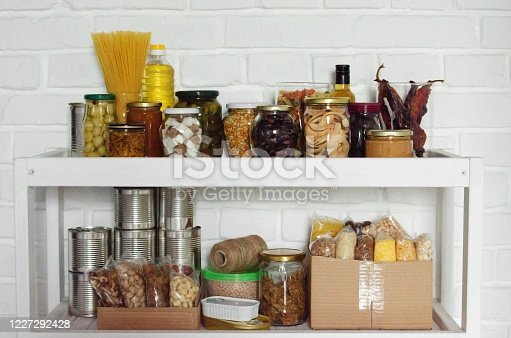 istock Set of long storage term foods on pantry shelf prepared for disaster emergency conditions on brick wall background 1227292428