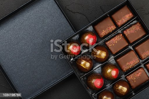 Set of luxury handmade bonbons in box on black background. Exclusive handcrafted chocolate candy. Product concept for chocolatier. Copy space
