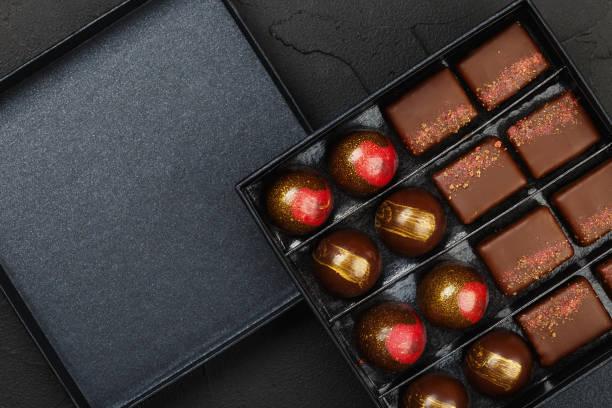 Set of luxury handmade bonbons in box on black background