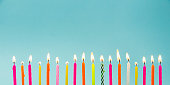 Set of many different color shape and pattern birthday candles burning isolated on blue. Happy Birthday card design concept.  Bottom lower border edge a lot of copy space.