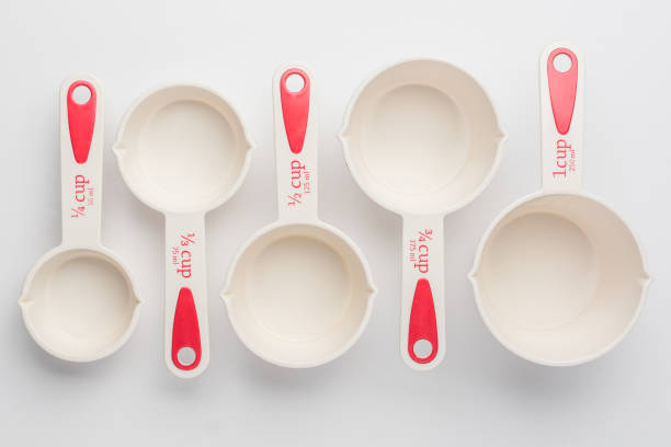 Set of Measuring Cups Staggered on White Background Top View Set of Measuring Cups Staggered on White Background Top View dry measure stock pictures, royalty-free photos & images
