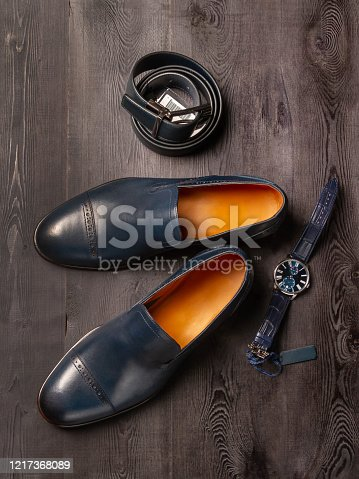 Classic Italian shoes in blue, elegant accessories for men. The texture of a dark abandoned tree. Selective focus, close up. View from above