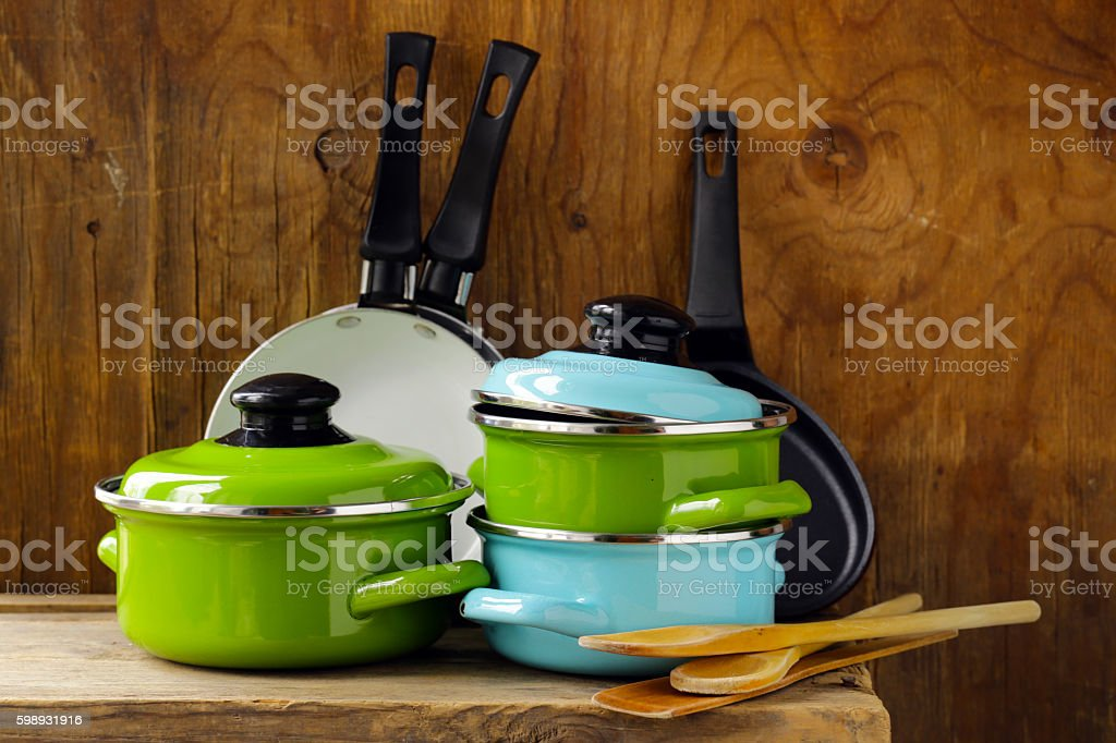 set of metal pots cookware on a wooden, domestic kitchen stock photo