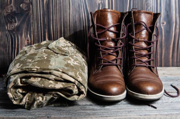 Set of military uniform on wooden background stock photo
