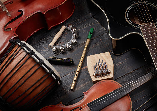 Set of musical instruments on dark wooden background Set of musical instruments on dark wooden background: guitar, violin, harmonica, cello and others. Top view folk music stock pictures, royalty-free photos & images