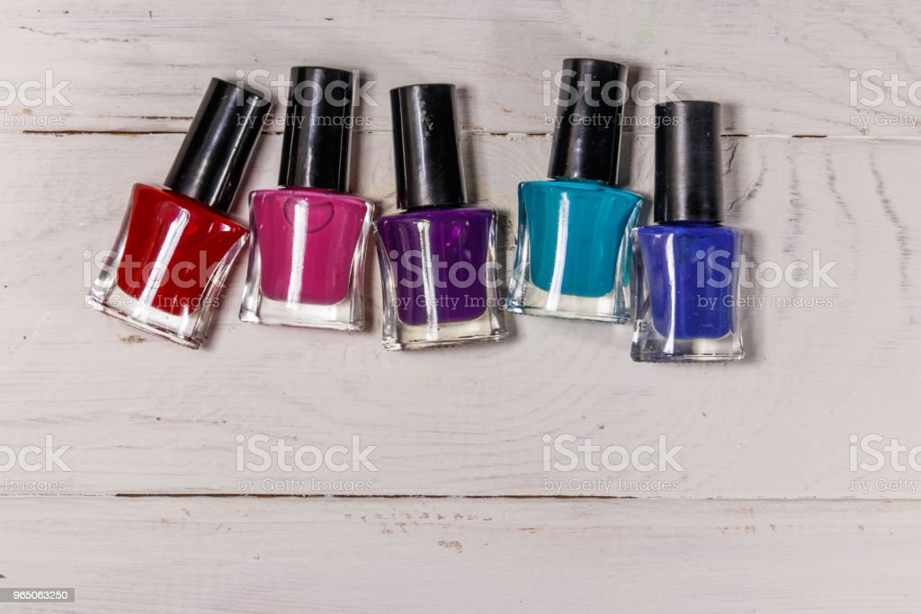 Set of nail polish bottles on white wooden background royalty-free stock photo