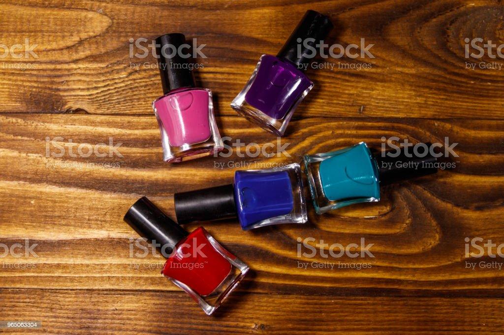 Set of nail polish bottles on wooden background zbiór zdjęć royalty-free