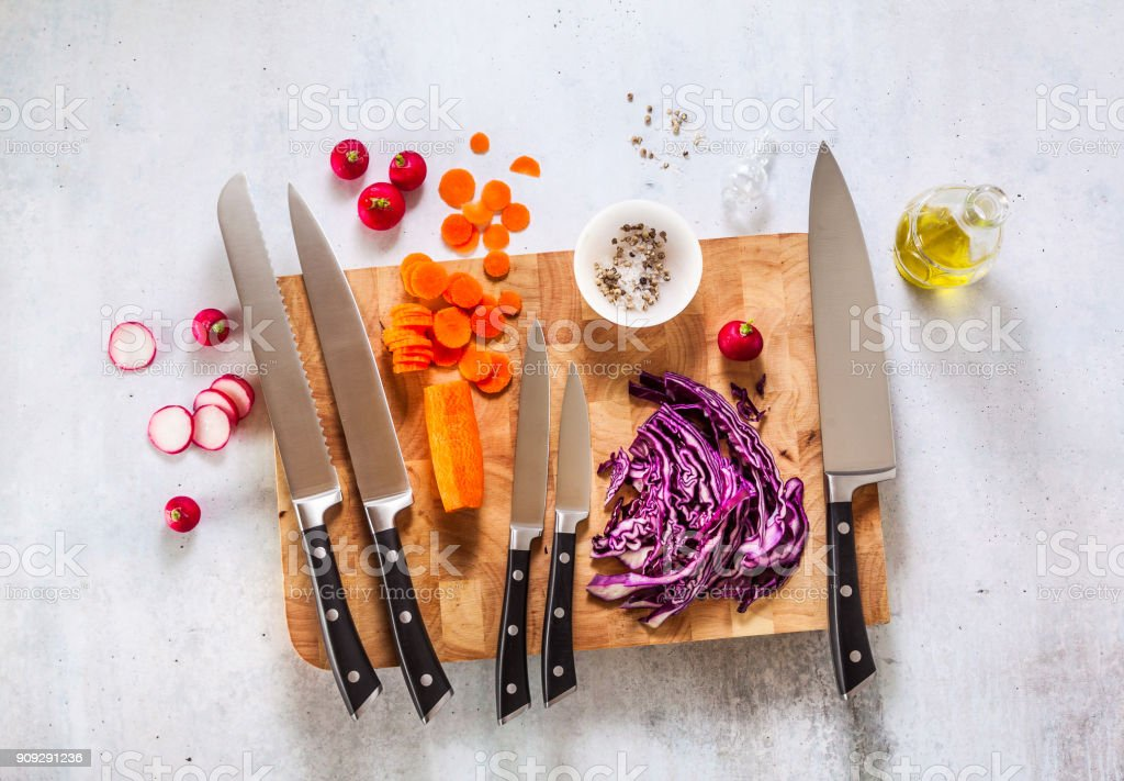 set of new professional kitchen knives on a wooden cutting board and vegetables stock photo