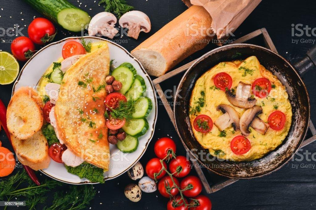 Eine Reihe von Omelette mit Gemüse, Pilzen und Huhn. Auf einem hölzernen Hintergrund. Ansicht von oben. Kopieren Sie Raum. - Lizenzfrei Brotsorte Stock-Foto