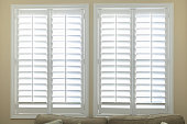 A set of open white plantation shutters in a light butter yelllow room