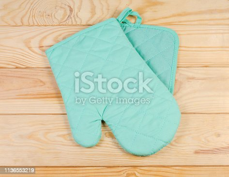 839034546 istock photo Set of oven glove and pot-holder on rustic table 1136553219