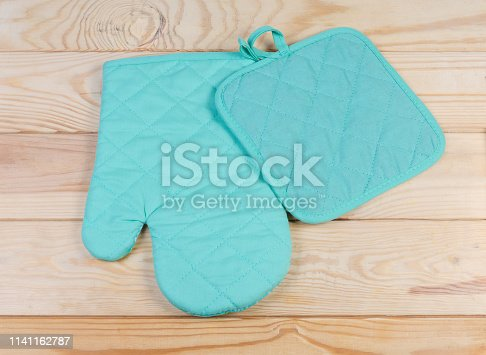 839034546 istock photo Set of oven glove and pot-holder on rustic table 1141162787