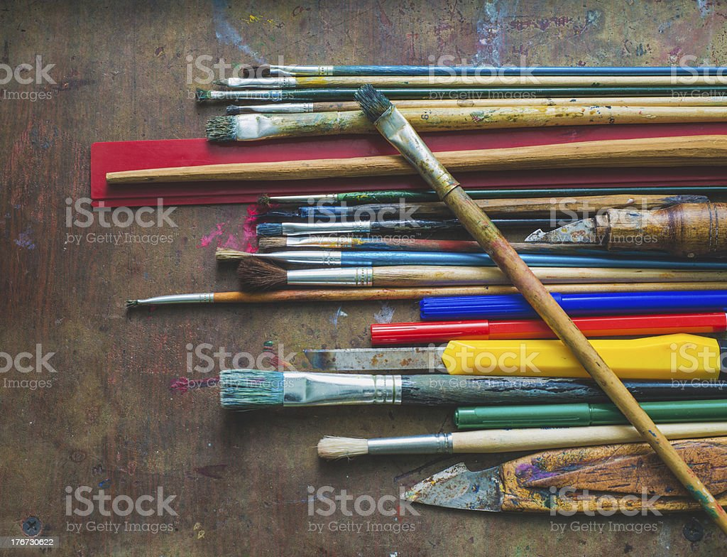 Set of paint brushes and office supplies on the table stock photo