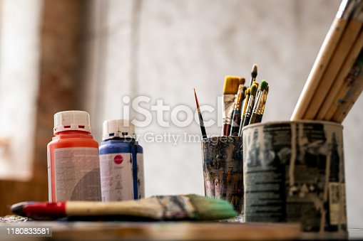 Set of paintbrushes in tin cans and two plastic jars with red and blue gouache on workplace of painter