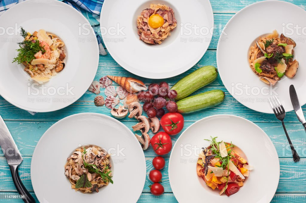 set of pasta at blue wooden background. italian cuisine flat lay....