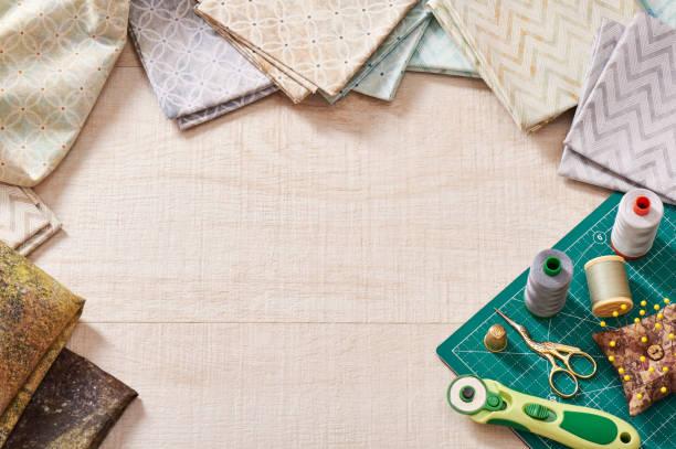 pastell stoffe und nähen tools auf handwerk matte, im mittleren bereich für text - patchworkstoffe stock-fotos und bilder