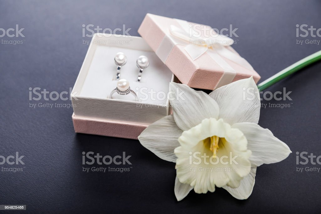 Set of pearl jewellery in gift box with flower on black background....