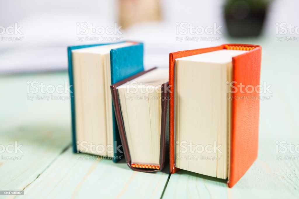 Set of pencils and pile of various books on wooden background. royalty-free stock photo