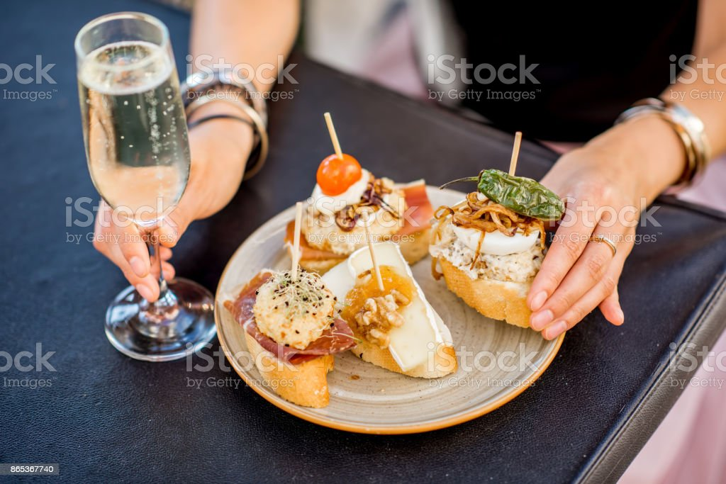 Set of pinchos on the table Beautiful and colorful set of pinchos, traditional spanish snack related to tapas, with glass of wine outdoors on the table Appetizer Stock Photo