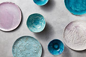 Ceramic bowls of different colors, sizes and types are empty on a gray concrete background. Flat lay of porcelain dishes handmade.
