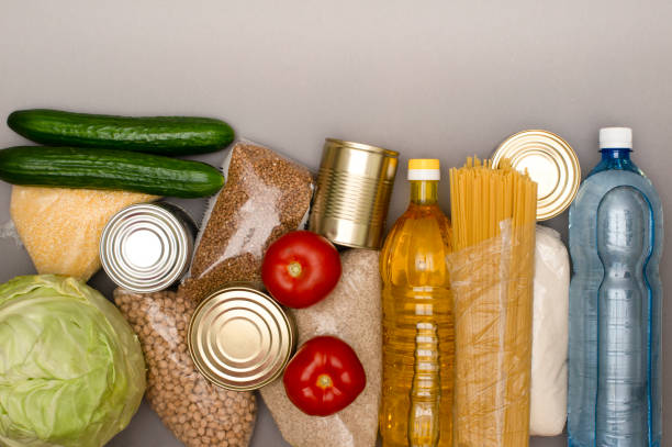 A set of products for delivery and donation. Cabbage, cucumbers, tomatoes, cereals, canned food, sunflower oil, a bottle of water. Place for text, copy space stock photo