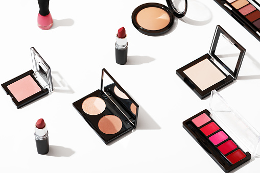 Set of professional cosmetics for fashionable makeup on white background isolated. Beauty industry products top view. Women's cosmetic accessories, lipstick, eye shadow, powder, blush and nail polish