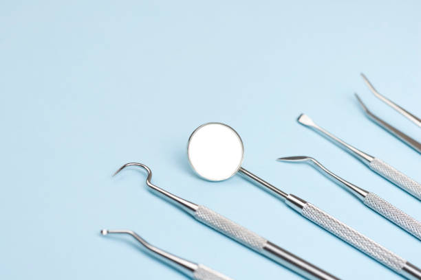 Set of professional dentist instruments on light blue background stock photo