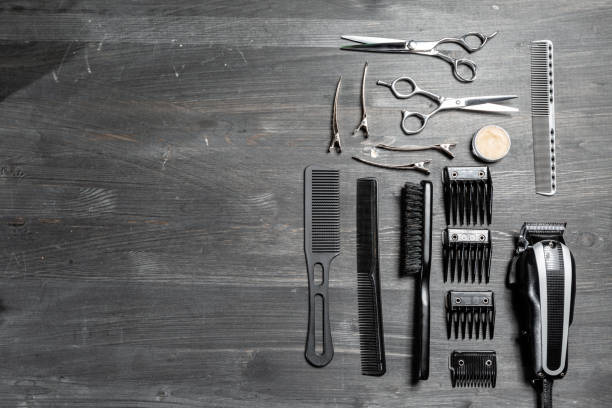 Set of professional hairdresser tools on grey background. Wooden table in barbershop. Working tool of barber master stock photo