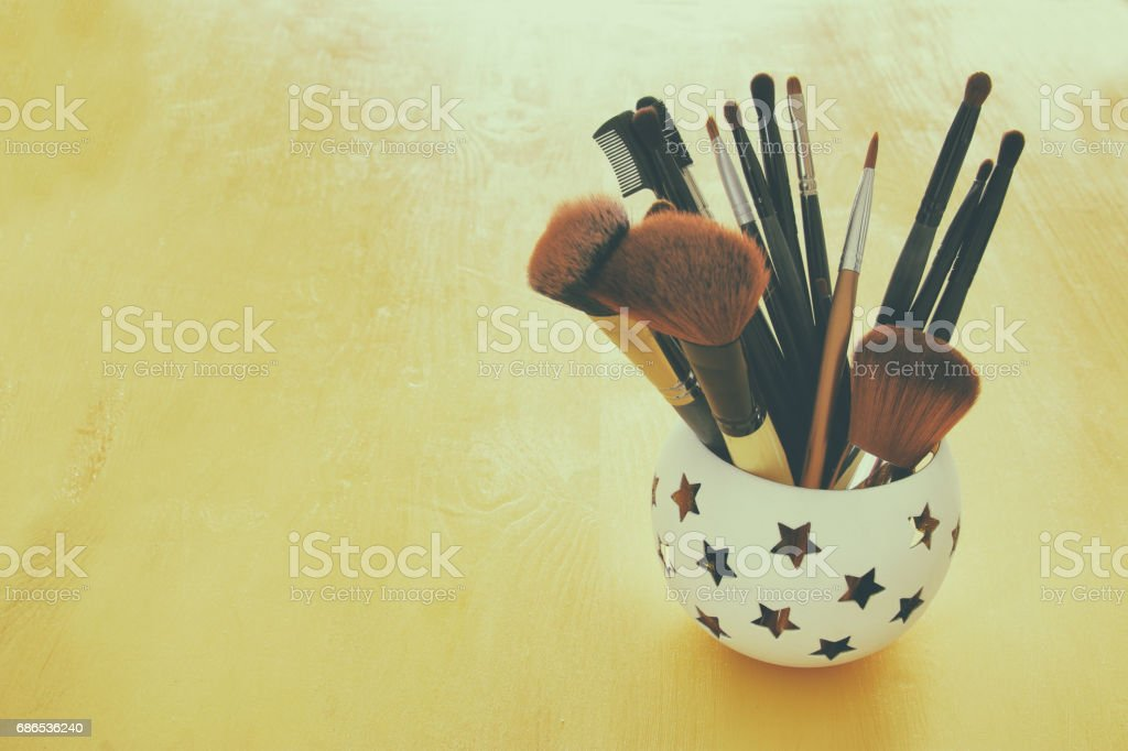 Set of professional makeup brushes on wooden table royalty-free stock photo