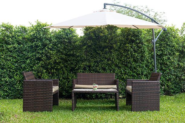 set aus rattan-möbeln aus unter einem großen garten regenschirm - sonnenschirm terrasse stock-fotos und bilder