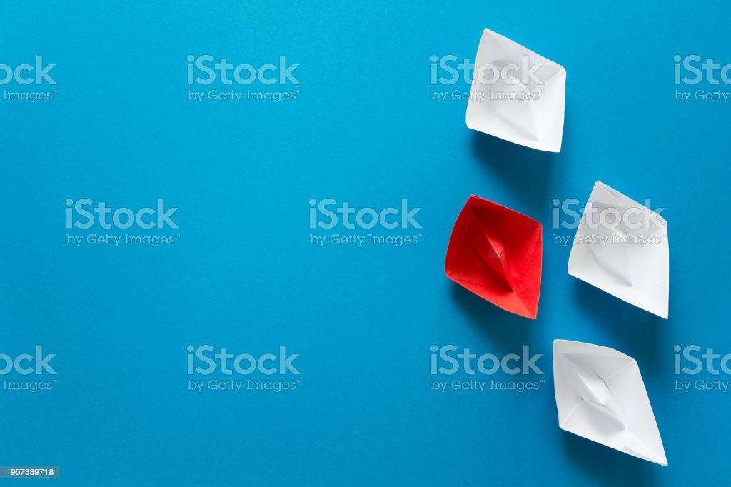 Set of red and white origami boats on blue paper background. Summer...